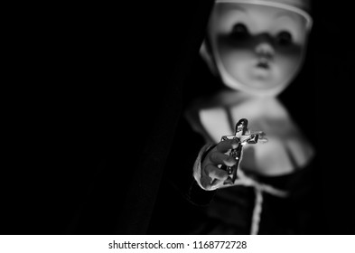 creepy nun doll hold a cross in hand in selective focus and high contrast concept