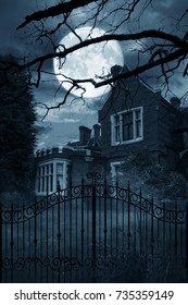 Creepy old house at night with iron gates, trees and a large moon