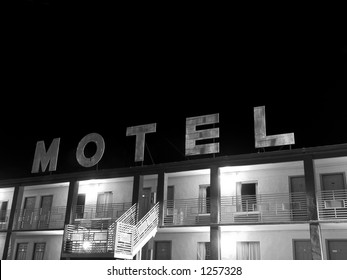 A creepy old motel sign in black and white.