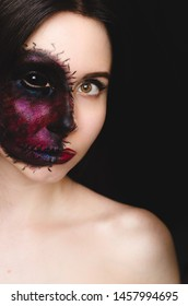 Creepy portrait of a woman with black eye and a cursed mark on her face on dark background. Demonic nature in an innocent body