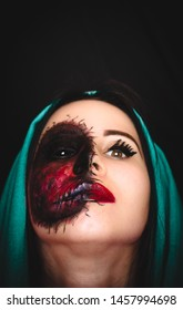 Creepy portrait of a woman with black eye and a cursed mark on her face on dark background with copy space. Demonic nature in an innocent body