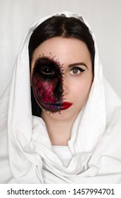 Creepy portrait of a woman with black eye and a cursed mark on her face on white background. Demonic nature in an innocent body