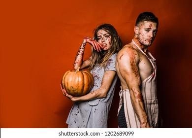 Creepy scary halloween vampire girl and big muscular man looking camera and holding pumpkin. Terrifying zombie couple. Concept image for Halloween. Scary undead zombie couple
