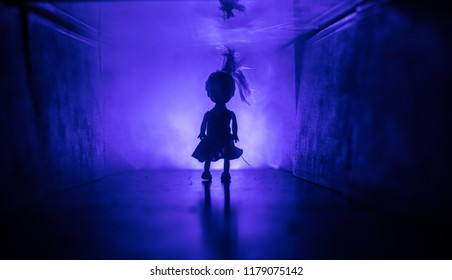 Creepy silhouette in the dark abandoned building. Horror about maniac concept or Dark corridor with cabinet doors and lights with silhouette of spooky horror doll standing with different poses.