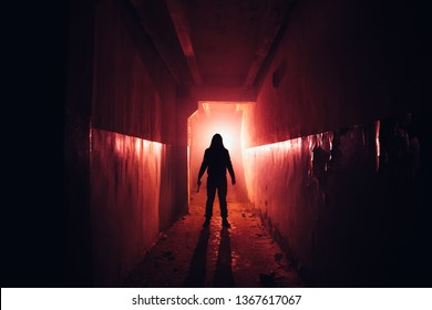 Creepy silhouette with knife in the dark red illuminated abandoned building. Horror about maniac concept.