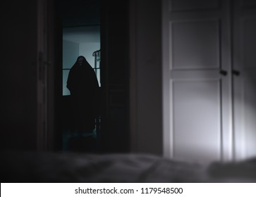 Creepy silhouette with skeleton face reflects in the mirror - Halloween background