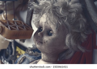Creepy sinister old broken dirty abandoned doll as halloween concept.
