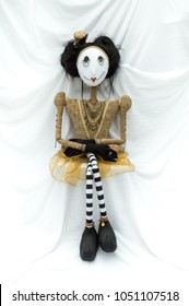 Creepy steampunk rag doll sitting facing forward. Legs crossed. Lifesize doll on a grungy white background. Part of a series of different poses. Vertical.