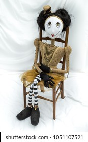Creepy steampunk rag doll sitting on wooden chair. Looking ahead. Lifesize doll on a grungy white background. Part of a series of different poses. Vertical.