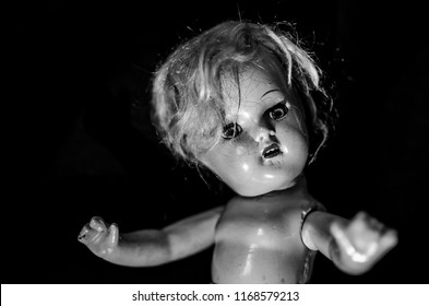 creepy vintage doll looking up in selective focus black and white and high contrast concept