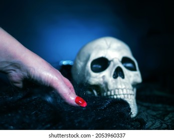Creepy witch hand with skull on dark background medium shot