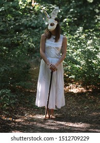 Creepy woman in rabbit mask in forest