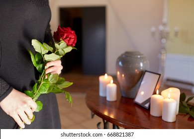 cremation, people and mourning concept - woman with red roses and cinerary urn at funeral in church