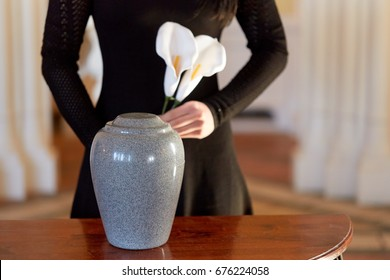 cremation, people and mourning concept - woman with flowers and cinerary urn at funeral in church