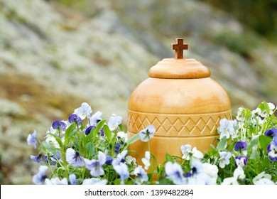 cremation urn surrounded by blue violets ready for spreading the ashes in nature