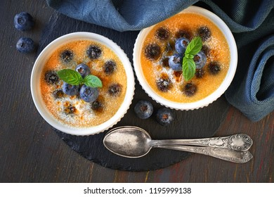 Creme brulee (cream brulee, burnt cream) with blueberry  powdered with sugar on dark rustic wooden background