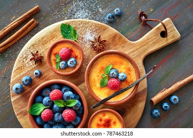 Creme brulee (cream brulee, burnt cream) bowls decorated with with raspberry, blueberry and mint on round wooden board