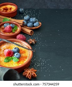 Creme brulee (cream brulee, burnt cream) with raspberry, blueberry and mint in terracota cazuela clay baking dishes on dark stone background. Border composition, space for your text.