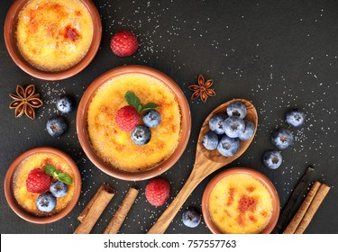 Creme brulee (cream brulee, burnt cream) with raspberry, blueberry and mint in terracota clay baking dishes. Top view, dark stone background.