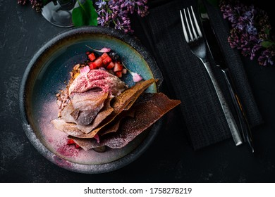 Creme brulee dessert with fresh strawberries on wooden background, sweet dessert with strawberries, blueberries, mango and fried caramel top view, flat lay