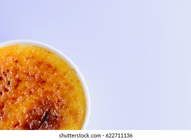 Creme brulee on grey background. Traditional French vanilla cream dessert with caramelised suger on top. Closeup. Top view.