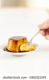 Creme caramel dessert or flan on white table. Hand holding a piece of delicious flan.