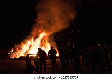 CREMONA, ITALY - FEBRUARY 14, 2018 - People's silhouette of crowd that gathers around a traditional carnival bonfire in the countryside.