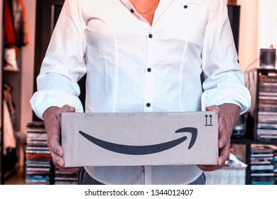 CREMONA, ITALY - MARCH, 2019: man holding cardboard box from Amazon. Amazon Prime is a fast paid delivery service.