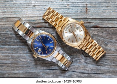 CREMONA, ITALY - MARCH, 2019: Rolex Oyster Perpetual Day-Date and Oyster Blue watch on wooden background. Rolex SA is a Swiss luxury company in the production of wristwatches, founded England in 1905