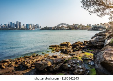 Cremorne Point, Sydney, Australia - September 11, 2018: Sydney Harbour shore walking trail- View from Cremorne Point with Opera House and Harbour Bridge and the rocky shore in the foreground.