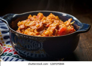 Creole bowl of chicken and andouille sausage Jambalaya with rice in dark moody rustic kitchen