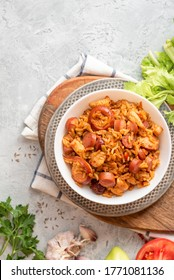 """Creole jambalaya (also called """"red jambalaya""""). Jambalaya with chicken, sausages and vegetables in a white bowl on a concrete background top view."""