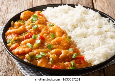 Creole shrimp Etouffee dish with celery, onion and pepper cooked in roux sauce served with rice close-up in a plate on the table. horizontal