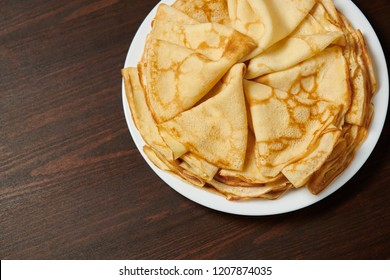 Crepe closeup, heap of thin pancakes on a dish, wood background