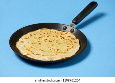 Crepe closeup, thin pancake on a frying pan, blue background