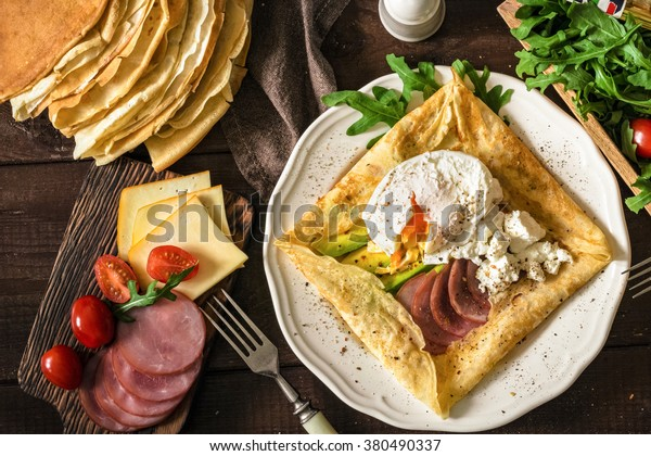 Crepe galette with ham, avocado, soft white cheese and poached egg on white plate. Sliced yellow cheese, pastrami, cherry tomatoes, green salad and stack of crepes on side. Top view