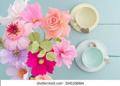 Crepe paper flower bouquet with cosmos, roses, echinacea and eucalyptus in a vase on light blue table with coffee cups shot from above