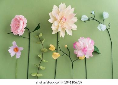 Crepe paper flowers dahlia, cosmos peony, sweet peas and eucalyptus on green background