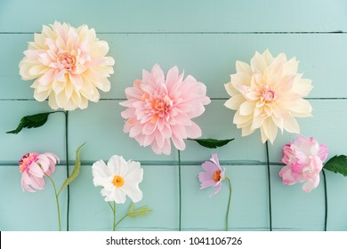 Crepe paper flowers dahlias, cosmos and echinacea on turquoise wooden background