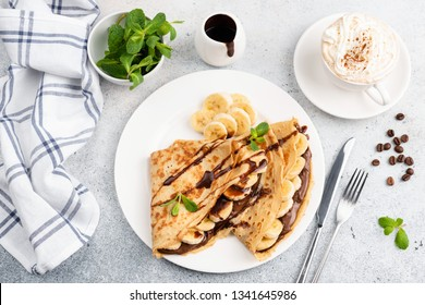 Crepes with banana, chocolate and cup of cappuccino on concrete background. Top view sweet breakfast food
