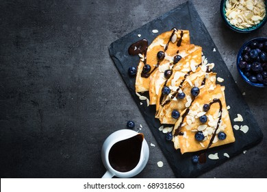 Crepes with blueberries almond flakes and chocolate sauce on black slate plate. Top view copy space.