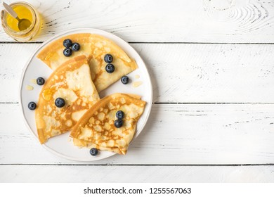 Crepes with blueberries and honey. Homemade pancakes, crepes on white wooden table, copy space.