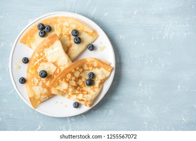 Crepes with blueberries and honey. Homemade pancakes, crepes on blue table, copy space.