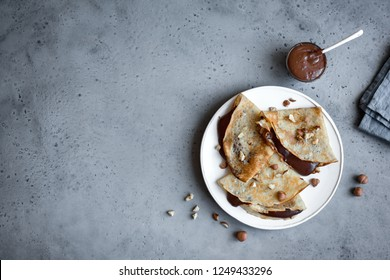 Crepes with chocolate spread and hazelnuts. Homemade thin crepes for breakfast or dessert on grey, copy space.