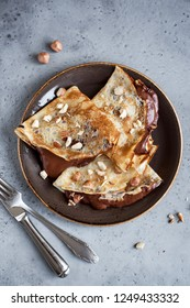 Crepes with chocolate spread and hazelnuts. Homemade thin crepes for breakfast or dessert, close up.