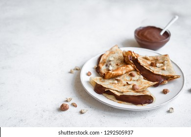 Crepes with chocolate spread and hazelnuts. Homemade thin crepes for breakfast or dessert on white background, copy space.