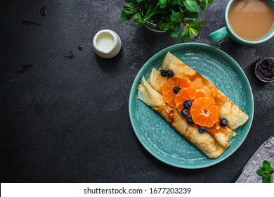 crepes with citrus, jam and berries (thin pancakes, mandarin, blueberry) menu concept. background. top view. copy space for text