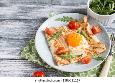 Crepes with eggs, cheese, arugula leaves and tomatoes.Galette complete. Traditional dish galette sarrasin