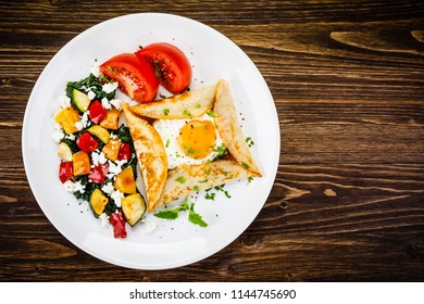 Crepes with eggs on wooden background