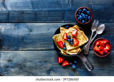 Crepes with fresh berries on rustic wooden background with space for text, top view. Pancake.